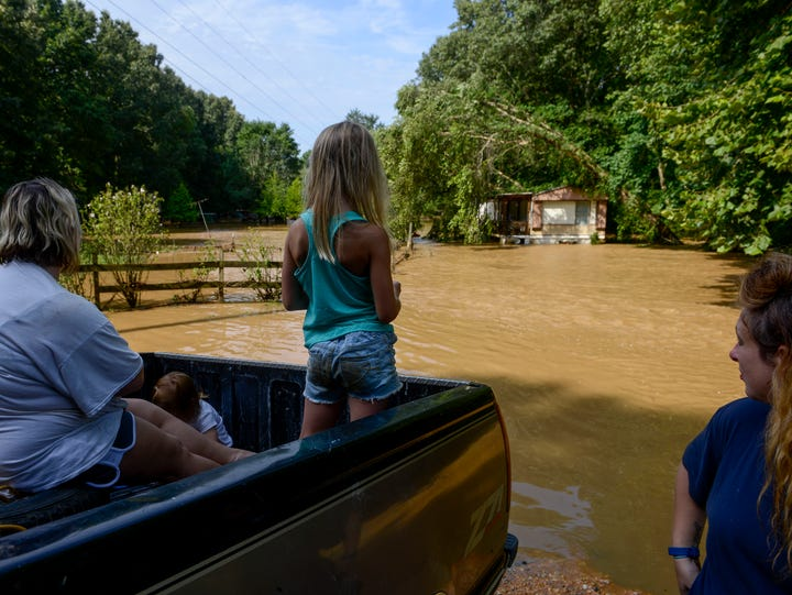 Aubree Northcott, center, 7, looks out over flood waters