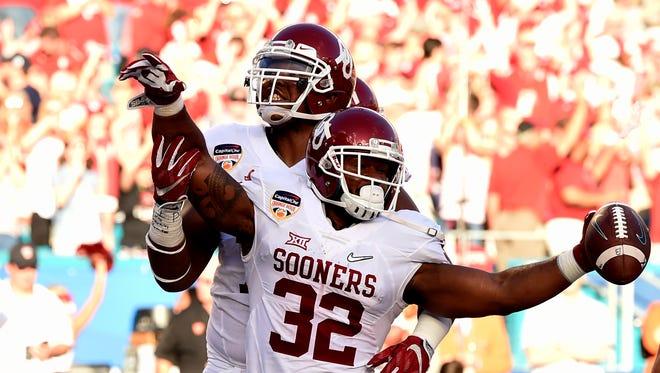 Oklahoma's Samaje Perine (32) and Orlando Brown celebrate Perine's first quarter touchdown run in the Orange Bowl on Thursday.