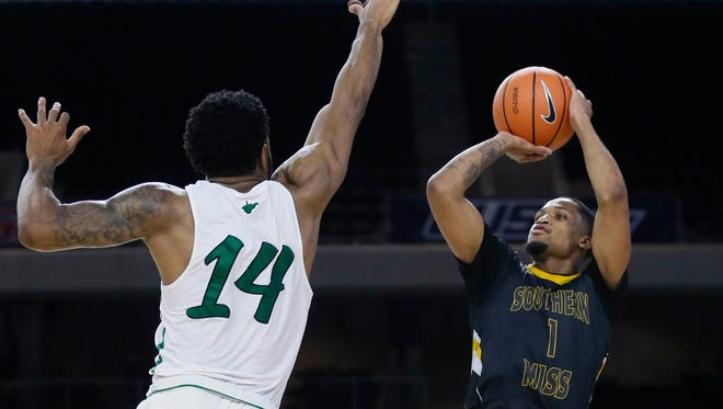 Southern Miss guard Cortez Edwards (1) shoots against Marshall Thundering Herd guard C.J. Burks (14) at last week's Conference USA tournament. Edwards, who was the Golden Eagles' leading scorer, also broke the school record for steals and minutes played.