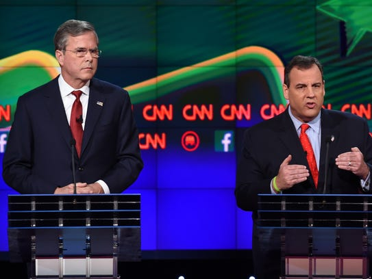 Chris Christie gestures as Jeb Bush looks on during