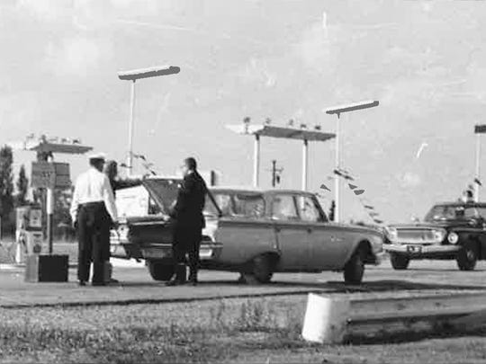 Winnebago County investigators examine the service station where Wayne Pratt was murdered in 1963. In the forefront is the home where Pratt lived.