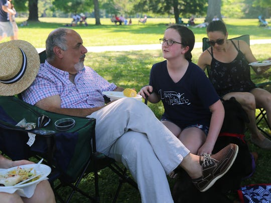 Grace Woodcock (right), 11, speaks with her grandfather, Joe Gasparini (left), on Sunday. The family set up around a blanket to eat food and talk.