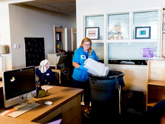 Custodian Debbie Doyle empties a trash can in the library during preparation for the upcoming school year at West High School in Knoxville on Friday, July 20, 2018. To bolster security, the school district is adding security officers to fill vacancies, upgrading camera systems at some schools and upgrading radio equipment to communicate with law enforcement and emergency personnel.