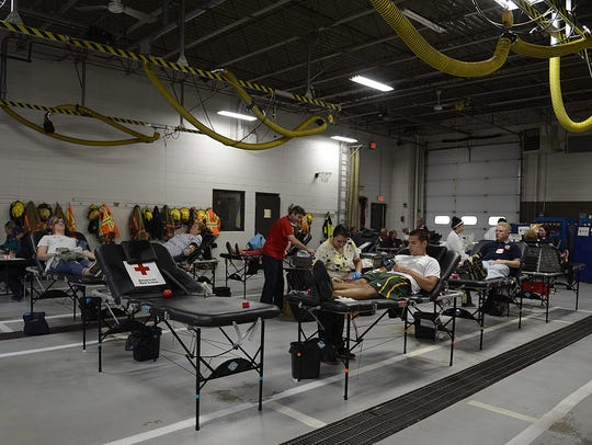 People give blood during a blood drive at the De Pere