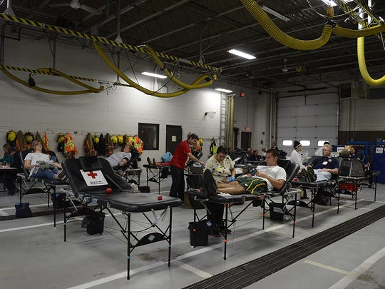 People give blood during a blood drive at the De Pere Fire Department on Friday,  The event was in honor of Jason Pansier, a Ledgeview fire captain and department president who lost a leg after a farming accident, and firefighters killed in the Sept. 11, 2001, terrorist attacks on the World Trade Center.