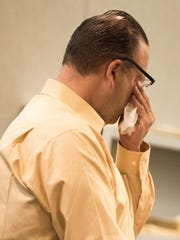 Hal Greenspan of Ocean Township wipes away tears as