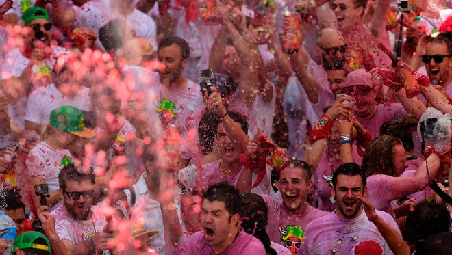 Revellers douse themselves with wine as they celebrate the 'Chupinazo' (start rocket) to mark the kickoff at noon sharp of the San Fermin Festival.