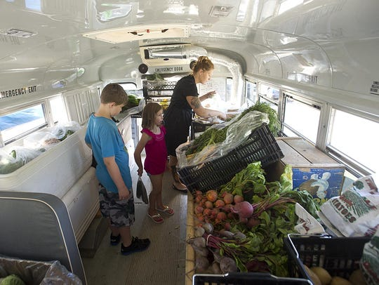 Billy, Lani and Keriann Krug pick out fresh produce