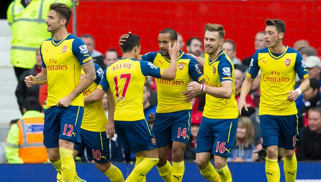 Arsenal's Theo Walcott (14) celebrates with teammates after his cross was deflected in for an own-goal.