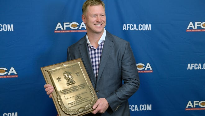 Scott Frost holds his Coach of the Year award during the American Football Coaches Awards Show.