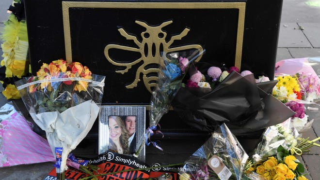 A photograph of victims Liam Curry and Chloe Rutherford is seen amongst floral tributes at the base of a 'tree of hope', planted as a memorial following the Manchester Arena bombing in central Manchester on May 22, 2018, the one year anniversary of the deadly attack.