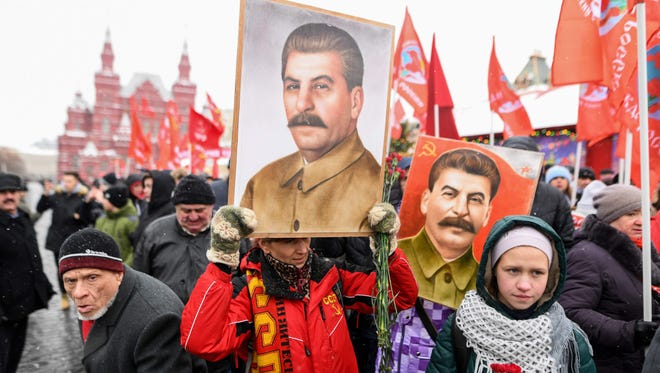 Russian Communist party supporters hold portraits of Soviet leader Joseph Stalin as they gather to mark the Stalin's 139th birthday on the Red Square, in Moscow, on Dec. 21, 2018.