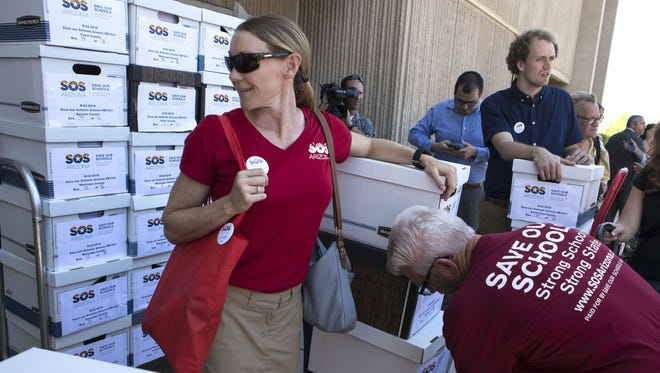 Karen Gresham from Save Our Schools Arizona is surrounded by boxes of signatures at the state Capitol on Aug. 8, 2017. The group delivered 111,540 signatures to refer the controversial expansion of Arizona's school-voucher program to voters in 2018.