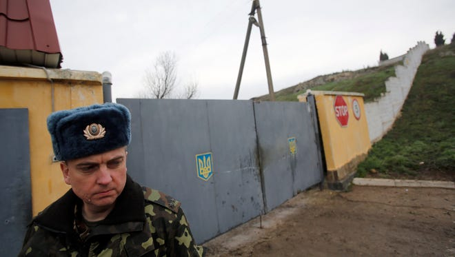 A Ukrainian officer stands outside the gate of a military base at the Black Sea port of Sevastopol in Crimea, Ukraine, March 8, 2014.