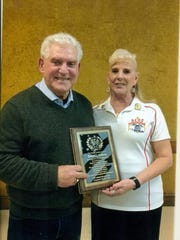 Exalted Ruler Arleen Hickman, right, presents Ed Andrews with the Outstanding Athlete and Coach Award.