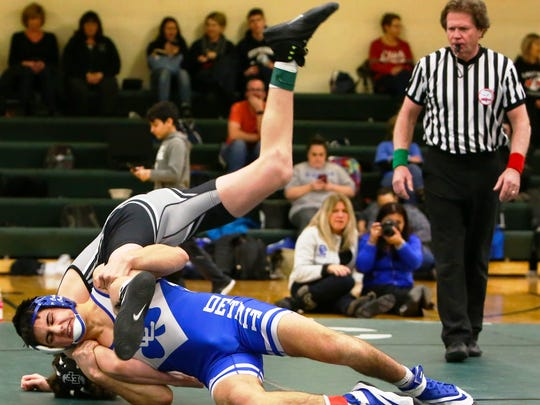 Catholic Central's Logan Sanom (top) won by technical fall over Edsel Ford's Ty Wyka in the 140 district final.