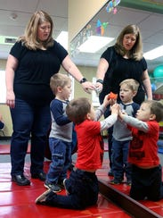 Tammy Harder with her twin boys Marcus, center, and Lucas, place stickers on a mirror at Kitsap Children's Therapy in Poulsbo. Marcus has received therapy since he was a baby after suffering a brain bleed while in the neonatal intensive care unit shortly after he was born.