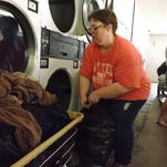 Maggie Pelow of Richmond get clothes dry for her family at Uptown Laundry with help from the Laundry Project.