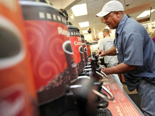 A customer helps himself to a cup of coffee at Wawa in New Castle.