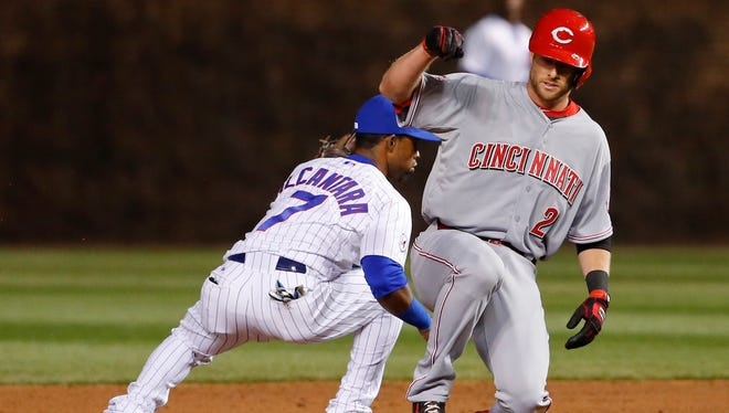 Reds shortstop Zack Cozart slides safely with a double as Cubs second baseman Arismendy Alcantara takes the throw during the seventh inning at Wrigley Field.