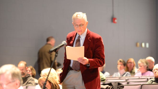 Bret Powell of Williston asks a question about a proposed pet attack law during a meeting Monday night at Williston Central School.