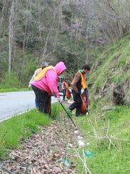 Volunteers work to pickup litter along Hayes Run Road