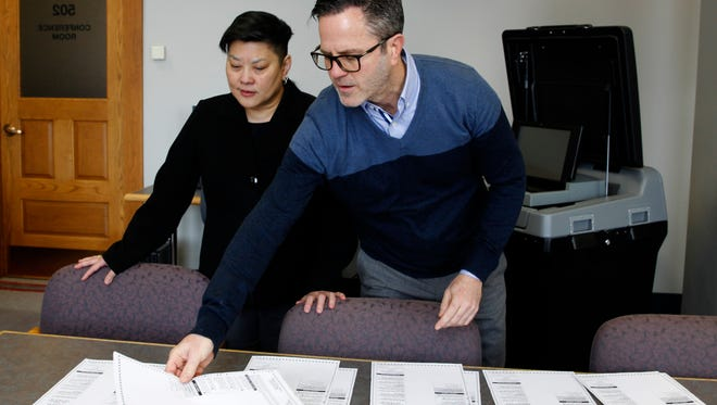 Terri Gabriel, deputy director of the Milwaukee  Election Commission, and Neil Albrecht, executive director, look  over test ballots used to validate the accuracy of  an electronic voting machine at City Hall.