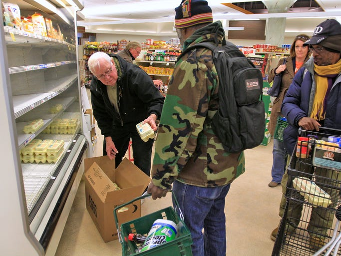 Marsh dairy clerk Jim Walden, left, hands cartons of eggs to customers, even before he can put them on the shelf at the downtown Marsh supermarket, Saturday, January 4, 2014. As meteorologists warn of 8-12 inches of snow and sub-zero temperatures, people have been flocking to stores to buy supplies.   Walden says it has been a long time since he's seen this kind of run on items in his department.  He has had to refill the egg shelves at least four or five times today, when he usually does it twice a day on a busy day.  Even as he restocked these, customers waited and took the cartons as soon as they hit the shelf.