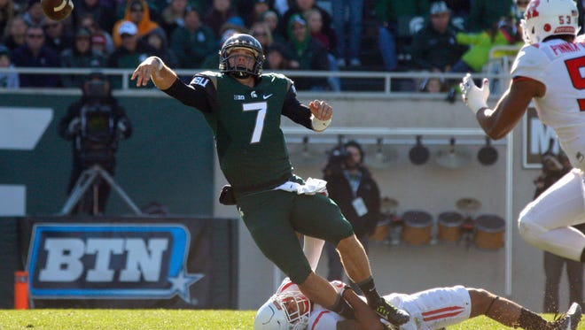Michigan State quarterback Tyler O'Connor (7) throws as he is tackled by Rutgers' Isaiah Wharton during the second quarter of an NCAA college footballl game, Saturday, Nov. 12, 2016, in East Lansing, Mich. (AP Photo/Al Goldis)