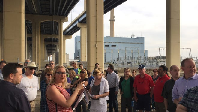 MichelleKramer, director of marketing and business development at Menomonee Valley Partners Inc., leads a recent tour of a valley redevelopment site. Part of itis beneath the High Rise Bridge, just across the Menomonee River from aWe Energies' power plant (background).
