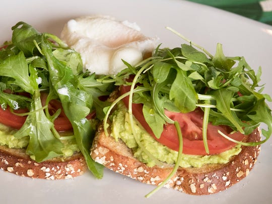 Avocado toast features multigrain toast slathered with fresh avocado, vine-ripe tomatoes, arugula and extra virgin olive oil served with two poached eggs at Meridian Cafe in Meridian Marketplace on the northeast corner of Pine Ridge and Livingston roads in North Naples.