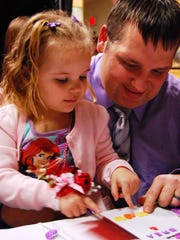 Jeff Mullins, of St. Clair, works on a Valentine with his daughter, Brea, 4, during a Daddy-Daughter Valentine's Dance in St. Clair.