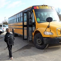 Penn Elementary fourth grader Kyra Stoddard and sixth grader Bobby Nicks find seats on a bus after school in North Liberty on Thursday, Feb. 4, 2016.