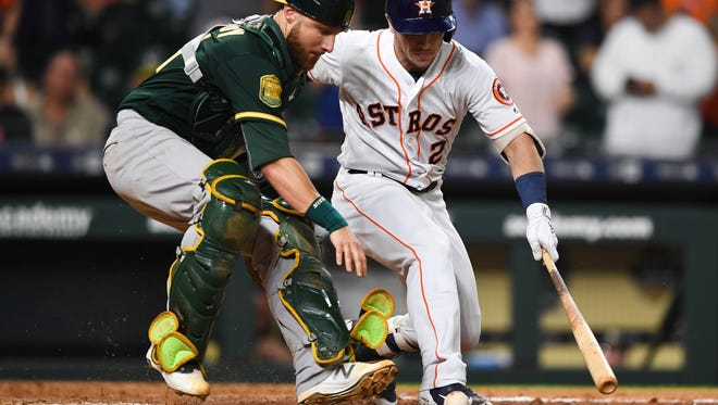 Athletics catcher Jonathan Lucroy chases the ball hit by Alex Bregman in the 11th inning at Minute Maid Park.