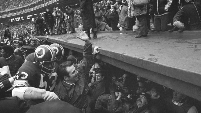 """FILE- In this Dec. 24, 1972, file photo, Washington Redskins coach George Allen waves to fans at Robert F. Kennedy Stadium in Washington as he leaves the field following the team's 16-3 win over the Green Bay Packesr in an NFL playoff game. At left is linebacker Harold McLinton. Washington's NFL team will get rid of the name """"Redskins"""" on Monday, July 13, according to multiple reports. It's unclear when a new name will be revealed for one of the league's oldest franchises. The team launched a """"thorough review"""" of the name July 3."""