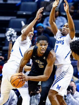 Memphis teammates Jimario Rivers (left) and Jeremiah Martin (right) apply defensive pressure against UCF forward  A.J. Davis (middle)  during first half action at the FedExForum in Memphis Tenn., Sunday, February 11, 2018.