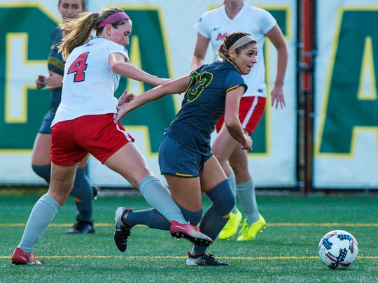 The University of Vermont's Savana Yurick, right, looks to pass the ball under pressure from Marist College's Alexa Svensson in Burlington on Tuesday, September 12, 2017.