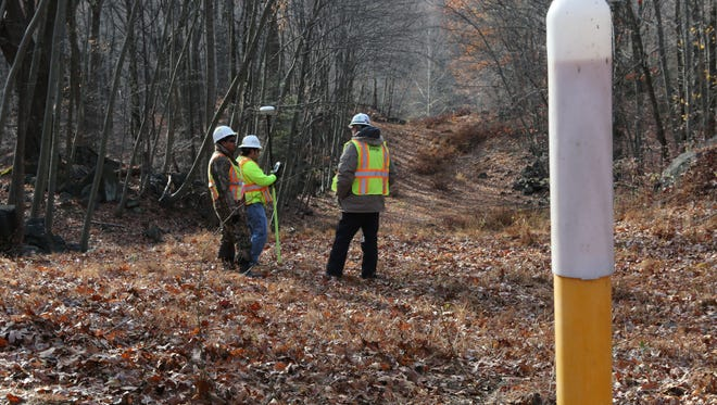 With a gas line marker in the foreground, a crew from Spectra Energy surveys an area on the existing gas pipeline easement in the Blue Mountain Reservation area in Cortlandt Nov. 20, 2014. The company is planning on replacement and partial rerouting of the Algonquin Pipeline through Westchester and Rockland.