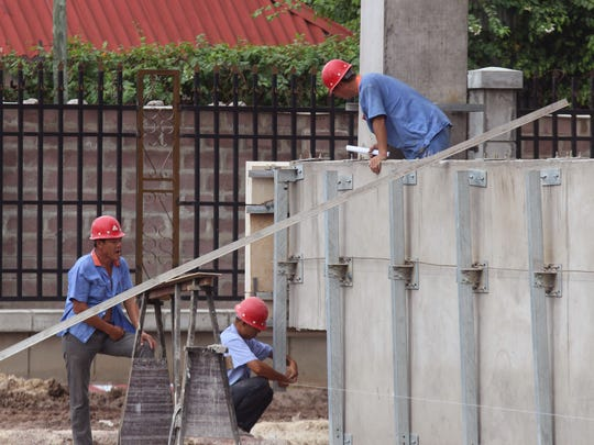 In this file photo dated May 20, 2015, Chinese workers at the building site of a new hotel to be used by Congo government officials when completed in Kinshasa, Democratic Republic of Congo.  Climate change could push more than 100 million people into extreme poverty by 2030 by disrupting agriculture and fueling the spread of malaria and other diseases, the World Bank said in a report Sunday Nov. 8, 2015, which also stated Carbon emissions are expected to rise for many years as China, India and other developing countries expand the use of fossil fuels to power their economies.