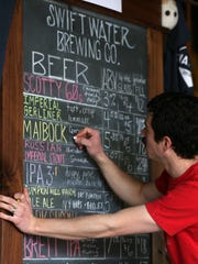 Patrick Meehan changes the menu to make way for a freshly tapped batch at Swiftwater Brewing.