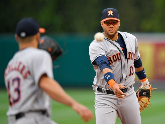 Houston Astros first baseman Yuli Gurriel, right, tosses the ball to starting pitcher Lance McCullers Jr. to get Los Angeles Angels' Kole Calhoun at first during the first inning of a baseball game, Saturday, May 6, 2017, in Anaheim, Calif. (AP Photo/Mark J. Terrill)