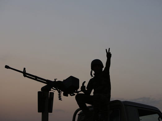 A Kurdish soldier flashes the victory sign as they battle against Islamic State militants on Aug. 18 near Mosul, Iraq.