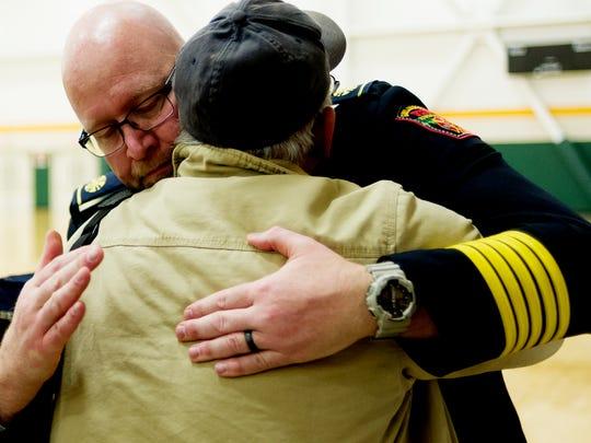 Gatlinburg Fire Chief Greg Miller hugs an attendee