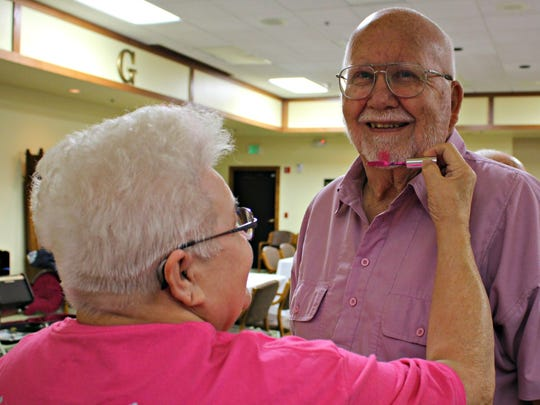 Resident Judi Wright adds a touch of pink to her neighbor Ken Ludwigsen's beard.