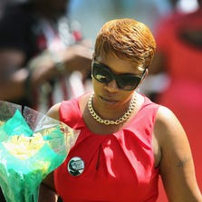 Lesley McSpadden, the mother of Michael Brown, walks from her son's grave Monday in St. Louis, Mo.
