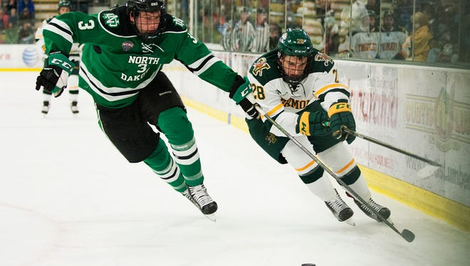 Catamount forward Anthony Petruzzelli (28) skates past North Dakota defenseman Tucker Poolman (3) with the puck during the men's hockey game between North Dakota and Vermont at Gutterson Fieldhouse on Friday night October 23, 2015 in Burlington.