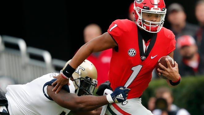 FILE - In this Saturday, Nov. 24, 2018, file photo, Georgia quarterback Justin Fields (1) tries to escape from Georgia Tech linebacker Victor Alexander (9) in the second half of an NCAA college football game in Athens, Ga. The NCAA quietly made a big change last year that helped quarterback Shea Patterson play for Michigan and will determine whether Justin Fields is eligible this fall at Ohio State. (AP Photo/John Bazemore, File)