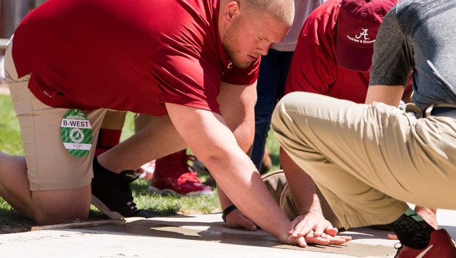 Bradley Bozeman puts his hand in cement during the Walk of Fame Ceremony at Denny Chimes on the University of Alabama campus in Tuscaloosa, Ala. on Saturday April 21, 2018.