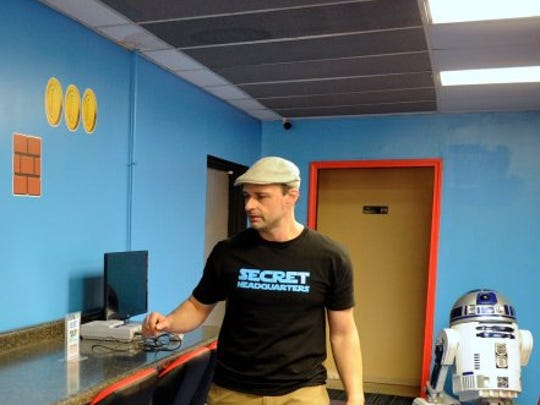 Secret Headquarters owner Jeff Osborne starts up some of the old school home game consoles available for play at the newly opened comic, toys, gaming and arcade at 4225 N. First Ave. in Evansville, March 18, 2016.