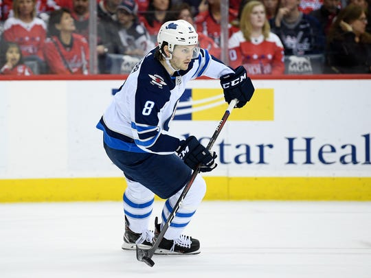 In this March 10, 2019, file photo, Winnipeg Jets defenseman Jacob Trouba (8) skates with the puck during the first period of an NHL hockey game against the Washington Capitals in Washington. (AP Photo/Nick Wass, File)